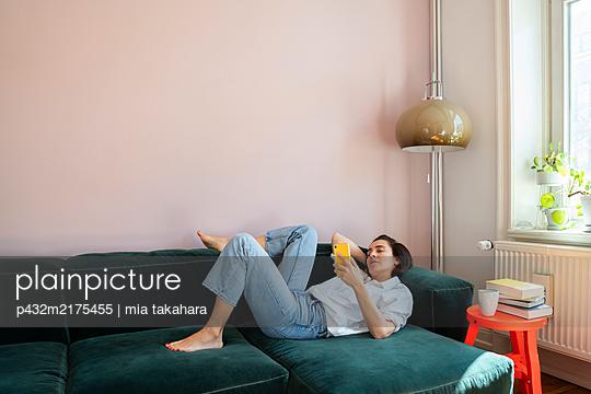 Frau liegt mit Iphone auf dem Sofa - p432m2175455 von mia takahara