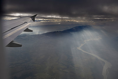 Airliner wing over mountains, mist and river - p1048m2088056 by Mark Wagner
