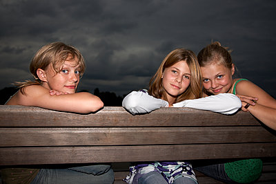 Three teenager sitting on bench - p1207m1111703 by Michael Heissner