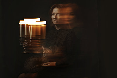 Painting like portrait of the surreal woman sitting on the chair and holding candlestick with cat on her knees - p1577m2289503 by zhenikeyev
