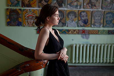 Young woman in black dress in the stairwell - p1646m2263450 by Slava Chistyakov