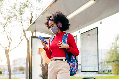 Young woman wearing headphones and protective face mask using smart phone while standing at bus stop - p300m2241281 by MANU RUIZ PHOTOGRAPHY