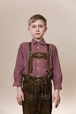 A serious boy wearing lederhosen - p301m844171f by Paul Hudson