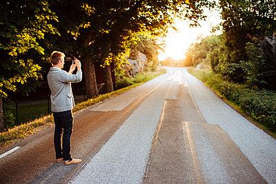 Man photographing a road at sunset in Bohuslan, Sweden - p352m1523655 by Benjamin Rudström