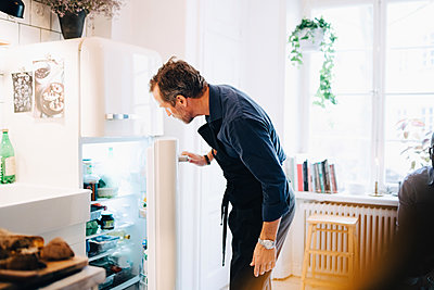 Mature man looking into refrigerator while standing at kitchen - p426m2018765 by Maskot