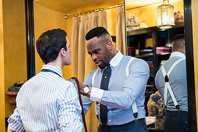 Tailor fastening customer's tie in tailors shop - p429m2004199 by G. Mazzarini