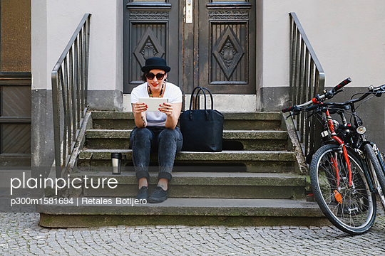 Woman sitting on stairs with coffee to go using tablet - p300m1581694 von Retales Botijero