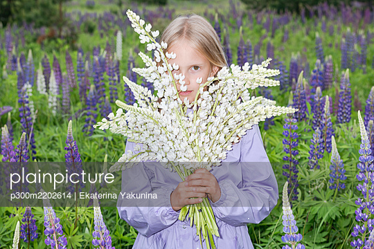 Portrait of girl standing in front of flower field holding bunch of white lupines - p300m2202614 by Ekaterina Yakunina