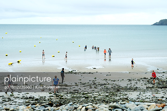 Group of people on beach - p378m2235560 by Kris Seraphin