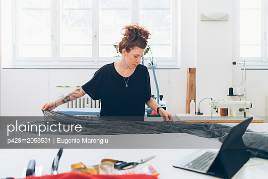 Fashion designer laying out fabric on workbench - p429m2058531 by Eugenio Marongiu