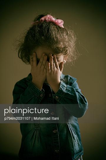 Trauriges kleines Mädchen mit Händen vor ihrem Gesicht - p794m2031107 von Mohamad Itani