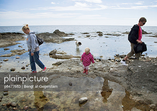 Family on rocks by the sea, Gotland, Sweden
