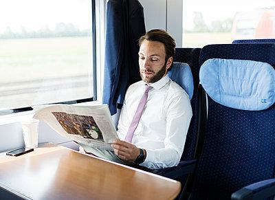 Geschäftsmann liest Zeitung im Zug - p1114m1159773 von Carina Wendland