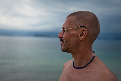 Man with eyeglasses looking out on the sea  - p1324m1441279 by Michael Hopf