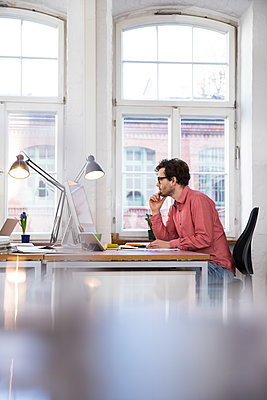 Man sitting at desk in office - p300m1459998 by Florian Küttler
