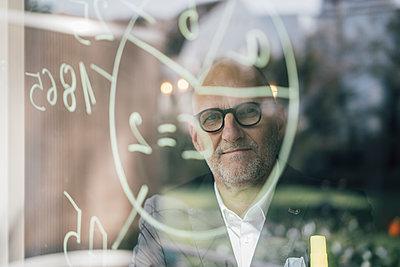 senior businessman brainstorming, drawing formulas on window pane - p300m1587524 von Gustafsson