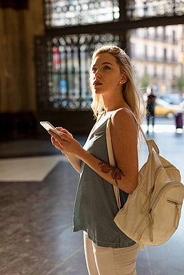 Young woman with cell phone and backpack in the city - p300m2070411 von Mauro Grigollo