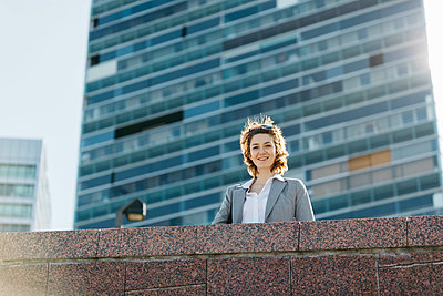 Successful young businesswoman standing at wall in front of office building - p300m2104004 by Josep Rovirosa