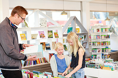Father with daughters in library - p312m2237255 by Phia Bergdahl