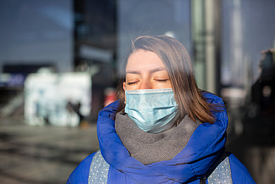 Young woman with surgical mask at railway station - p975m2245772 by Hayden Verry