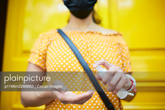 unrecognizable woman wearing a face mask and applying hands sanitizer - p1166m2268883 by Cavan Images