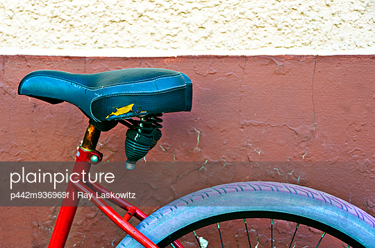 Louisiana, New Orleans, A worn down bicycle is parked by a textured wall. - p442m936969f by Ray Laskowitz