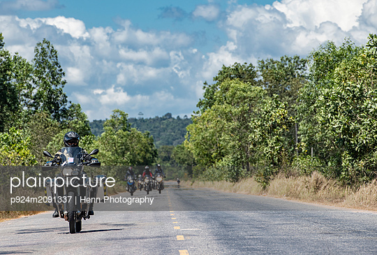 Male friends riding ADV motorcycles on rural road in Cambodia - p924m2091337 by Henn Photography