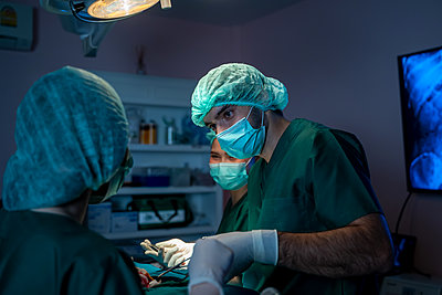 Medical team of surgeons in hospital working with electrocautery - p1166m2269024 by Cavan Images