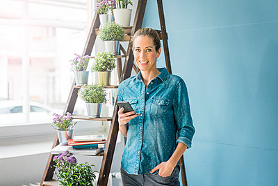 Beautiful woman in her home, decorated with plants, holding smartphone, smiling - p300m1568290 by Robijn Page