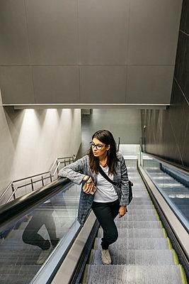 Businesswoman standing on escalator of a subway station - p300m2156373 by Josep Rovirosa