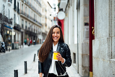 Mid adult woman holding reusable cup while standing at street in city - p300m2267876 by Miguel Angel Partido Garcia