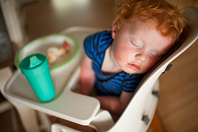 High angle view of cute baby boy with food and drink sleeping on high chair at home - p1166m2105835 by Cavan Images