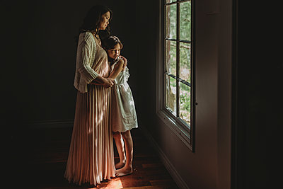 Mother and daughter embrace and looking out studio window - p1166m2130972 by Cavan Images