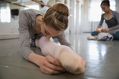 Female ballet dancer stretching leg, warming up in dance studio - p1192m1403447 by Hero Images