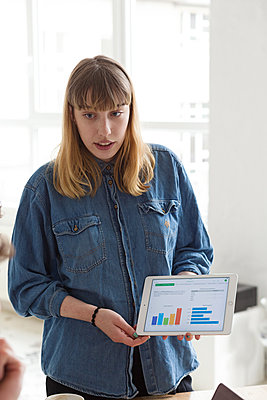 Junge, blonde, moderne Frau erklärt eine Graphik auf Ihrem Ipad - p1301m2021023 von Delia Baum