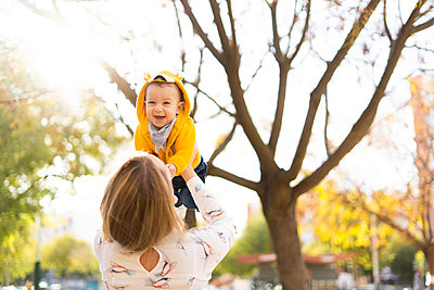 Mother lifting up happy baby boy in a park - p300m2155917 by Eloisa Ramos