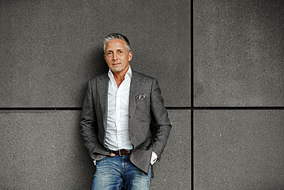 Male entrepreneur with hands in pockets leaning on gray wall - p300m2282810 by Sandro Jödicke