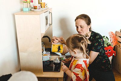 Mother with daughter playing tea party - p312m2207719 by Stina Gränfors