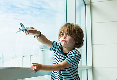 Caucasian boy playing with toy airplane near window - p555m1522719 by Marc Romanelli
