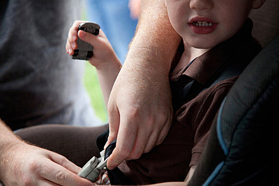 Boy being strapped into car safety seat - p924m700358 by Flynn Larsen