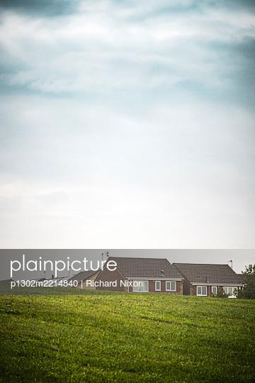 Modern detached houses behind a grassy hill - p1302m2214840 by Richard Nixon