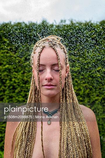 Junge Frau mit Dreadlocks im Garten - p1508m2099875 von Mona Alikhah