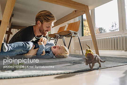Father and son playing under the table at home - p300m2167238 by Kniel Synnatzschke