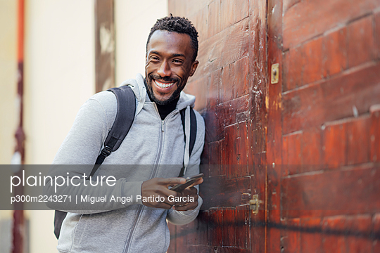 Young man with backpack and mobile phone smiling while leaning on wall - p300m2243271 by Miguel Angel Partido Garcia