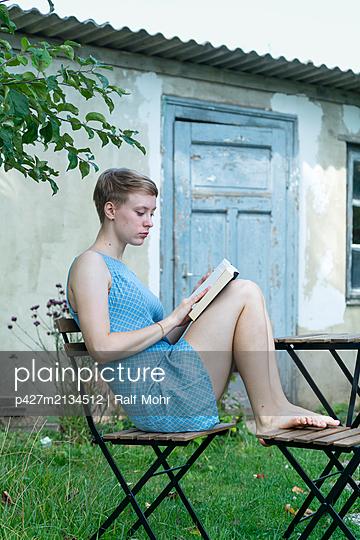 Junge Frau liest ein Buch im Garten - p427m2134512 von Ralf Mohr