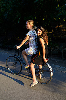 Two friends on a bike in the evening sun  - p276m2115912 by plainpicture