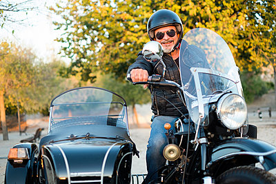 Portrait of smiling biker wearing helmet and sunglasses on his sidecar motorcycle - p300m1192192 by Jaen Stock