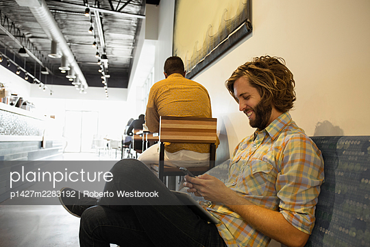Young man sitting in coffee shop using smartphone - p1427m2283192 by Roberto Westbrook