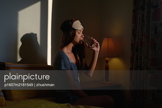 Woman sit on bed and drink water from glass in sleeping mask in her bedroom - p1607m2181549 by zhushman