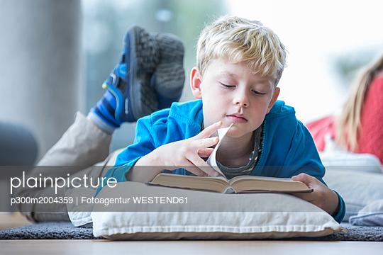 Schoolboy lying on the floor reading book in school break room - p300m2004359 von Fotoagentur WESTEND61